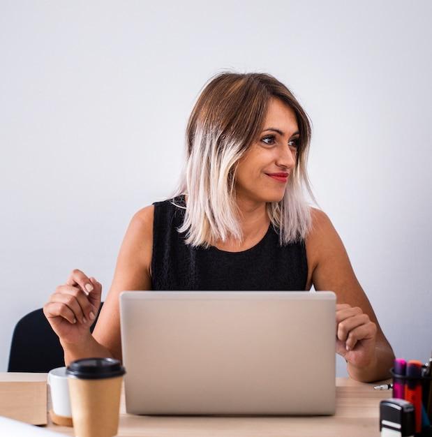 Femmina di vista frontale sul lavoro facendo uso del computer portatile Foto Gratuite