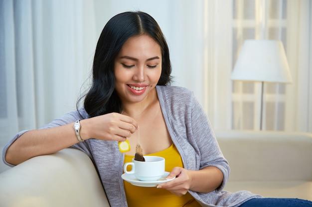 Femmina filippina sorridente che fa tè sullo strato Foto Gratuite