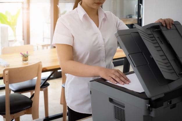 Femmina giovane in uniforme in uniforme usa stampante per scansionare documenti importanti e riservati in ufficio Foto Premium