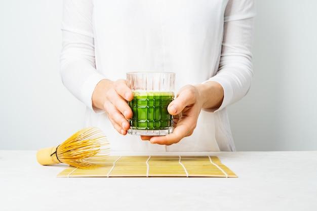 Femmina in abiti bianchi tenendo il bicchiere con tè matcha giapponese o frullato verde Foto Premium