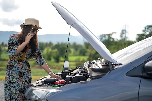 Femmina in strada con auto rotta che richiede aiuto Foto Premium