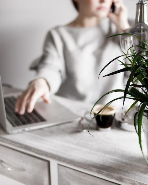 Femmina in un maglione grigio, parlando al telefono con la mano su un computer portatile e caffè sul tavolo Foto Gratuite