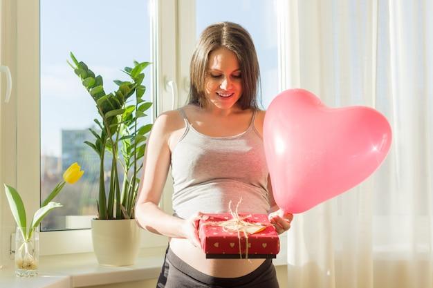 Femmina incinta felice con il contenitore di regalo dei biglietti di s. valentino e l'aerostato rosso del cuore Foto Premium