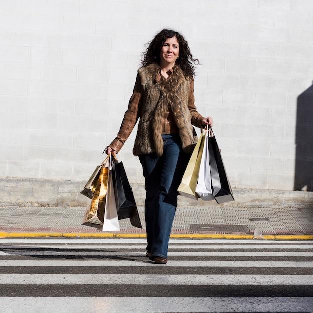 6c7dde2813e9 Femmina ispanica che cammina con i sacchetti della spesa Foto Gratuite
