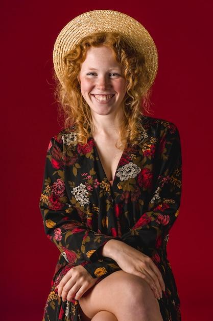 Femmina rossa con cappello sorridente e seduto con le gambe incrociate Foto Gratuite