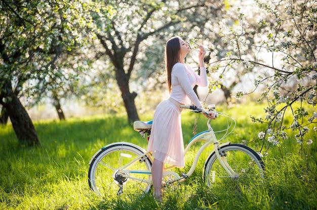 Femmina sexy con una bici in un giardino di primavera Foto Premium