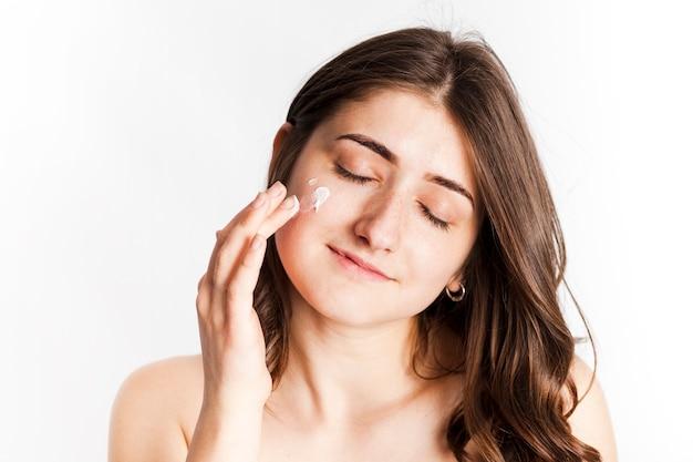 Femmina sorridente che applica crema per il viso Foto Gratuite
