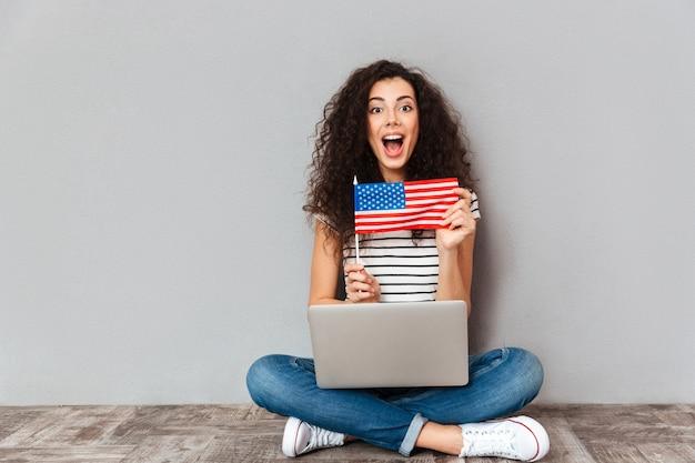 Femmina splendida con il bello sorriso che si siede nella posa del loto con il computer d'argento sulle gambe che dimostrano bandiera americana sopra la parete grigia Foto Gratuite