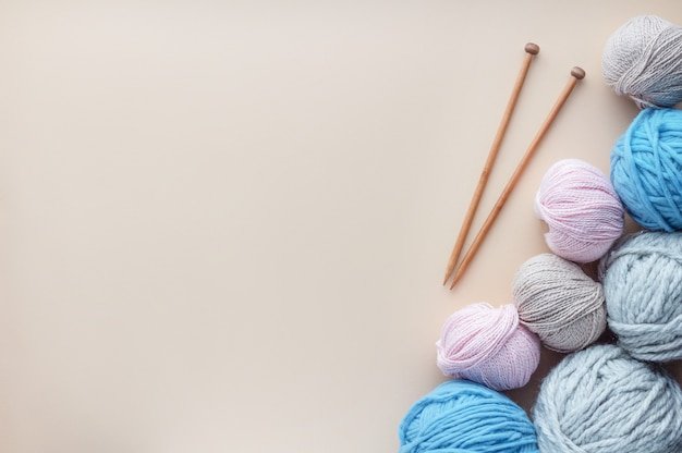 Ferri da maglia che si trovano vicino ad un mazzo di filato su fondo pastello. Foto Premium