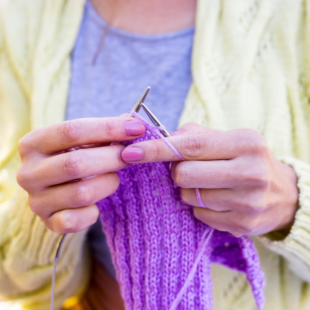 Ferri da maglia per maglieria in mani femminili sono articoli in maglia di colore lilla Foto Premium
