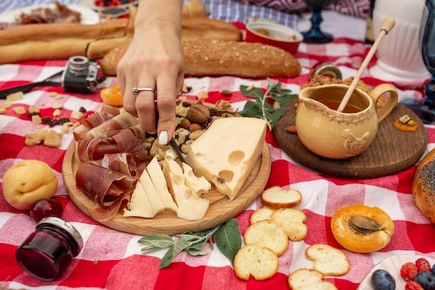 Festa all'aperto per picnic all'aperto. cibo, miele e frutta giacevano su una coperta a scacchi. Foto Premium