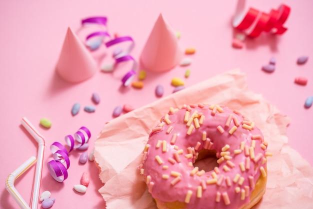 Festa. ciambelle glassate rotonde zuccherate variopinte su fondo rosa. cappellino celebrativo, orpello, caramelle Foto Premium