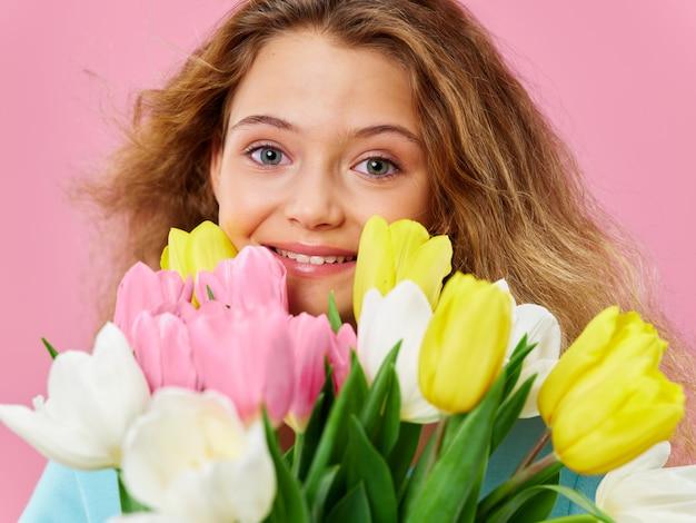 Festa della mamma, una giovane donna con un bambino in posa con fiori, un regalo per la festa della donna e la festa della mamma Foto Premium