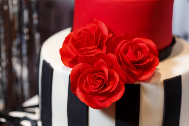 Festa di compleanno con bella torta grande, decorata con rose e in piedi sulla canna. gustosi dolci con decorazioni color crema nei colori nero, rosso, bianco Foto Premium