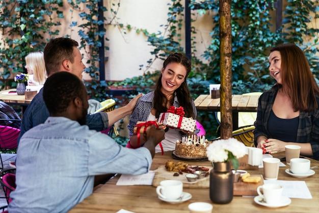 Festa di compleanno di una ragazza sulla terrazza di un caffè con regali dai migliori amici Foto Gratuite