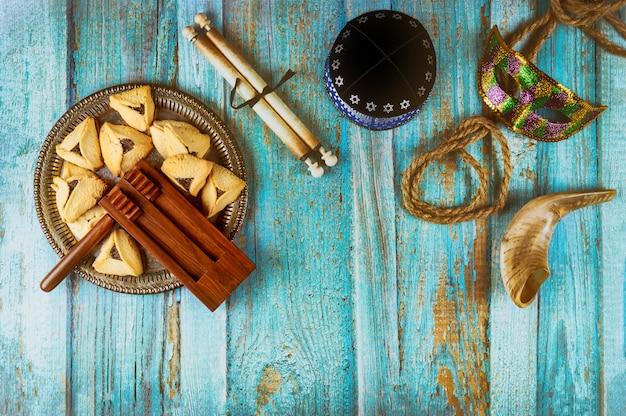 Festa ebraica purim con biscotti hamantaschen orecchie hamans, maschera di carnevale e kippa pergamena, corno Foto Premium