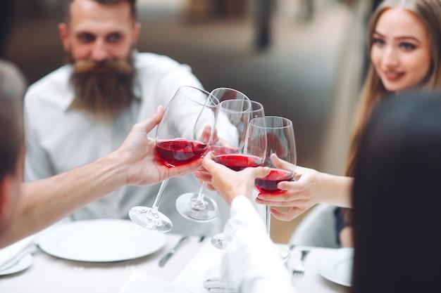 Festa. gli amici bevono vino in un ristorante. Foto Premium