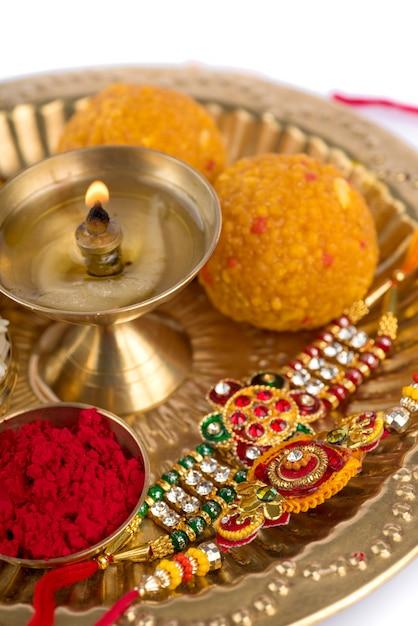 Festival indiano: rakhi con chicchi di riso, kumkum, dolci e diya sul piatto con un elegante rakhi. un tradizionale cinturino da polso indiano che è un simbolo di amore tra fratelli e sorelle Foto Premium