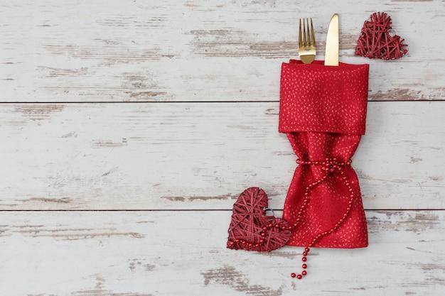 Festosa tavola per san valentino con forchetta d'oro e coltello e decorazioni. Foto Premium