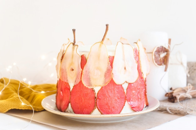 Festosa torta bianca decorata con fette di pera rossa e bianca Foto Premium