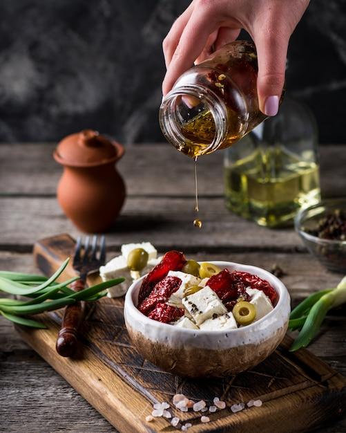 Feta al formaggio greco con erbe e olive, pomodori secchi. Foto Premium