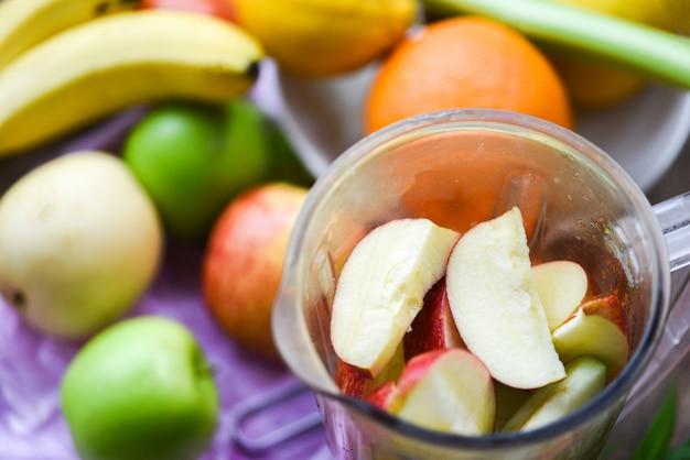 Fetta della frutta fresca nel miscelatore che prepara gli ingredienti sani di estate del succo nella cucina Foto Premium