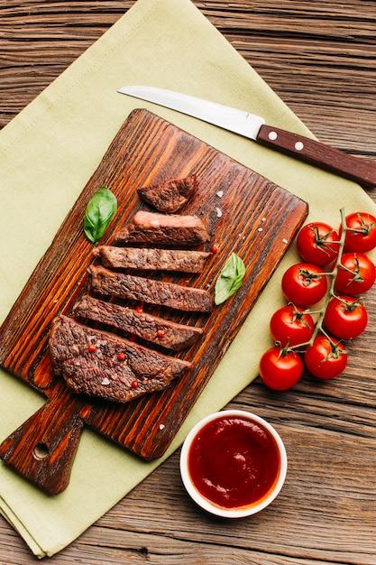 Fetta di bistecca fritta con salsa di pomodoro rosso sul tagliere di legno Foto Gratuite