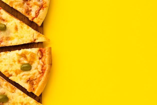 Fetta di pizza sul piatto di legno su sfondo giallo Foto Gratuite