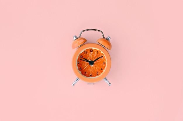 Fetta di pompelmo fresco in piccola sveglia arancione Foto Premium
