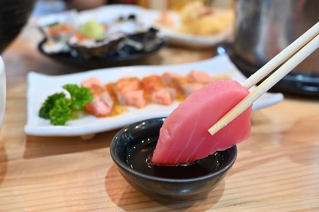 Fetta di sashimi di tonno sulle bacchette. Foto Premium