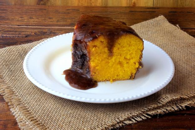 Fetta di torta di carote con rivestimento di cioccolato sul piatto in ceramica bianca Foto Premium