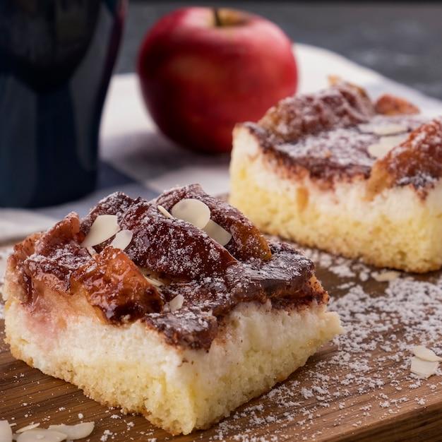 Fetta di torta di mele fatta in casa scaglie di mandorle e zucchero a velo Foto Premium