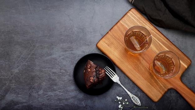 Fetta di torta e tazze di tè su un supporto di legno su una terra posteriore grigia Foto Gratuite