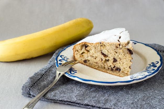 Fetta di torta o pane di banana casalinga sul piatto decorato con la banana gialla organica Foto Premium