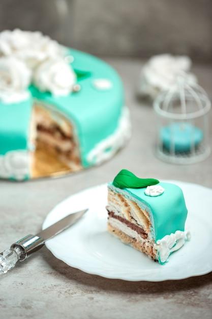 Fetta di torta turchese decorata con rose bianche e foglie verdi Foto Gratuite