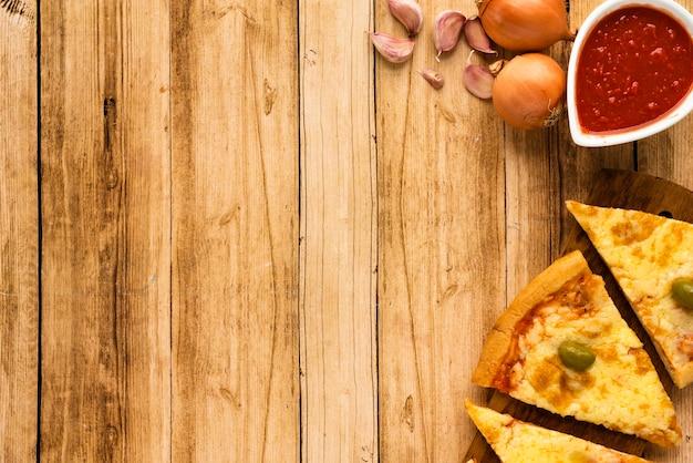 Fetta e salsa della pizza con l'ingrediente crudo su superficie di legno Foto Gratuite