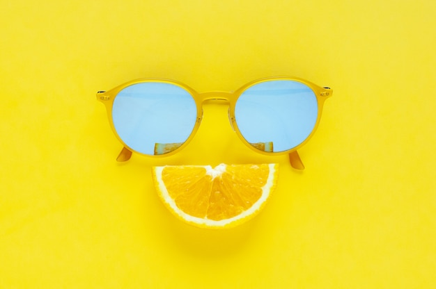Fetta set di frutta arancione come bocca sorriso e occhiali da sole gialli su sfondo giallo. Foto Premium
