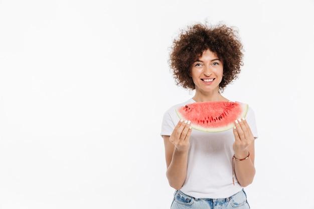 Fetta sorridente felice della tenuta della donna di un'anguria Foto Gratuite