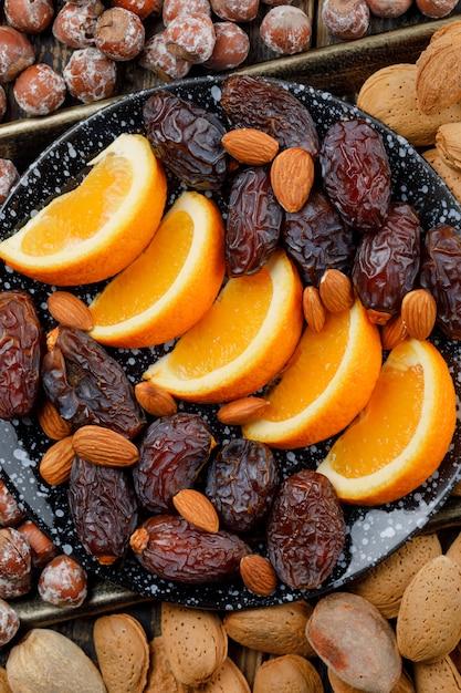 Fette d'arancia con datteri, mandorle e noci in un piatto sul vassoio di rame Foto Gratuite