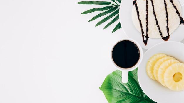 Fette di ananas; tortillas e caffè bere sulle foglie verdi su sfondo bianco Foto Gratuite