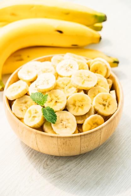Fette di banana gialla cruda in ciotola di legno Foto Gratuite
