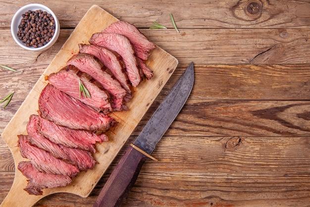 Fette di carne arrosto di manzo rara media sul tagliere di legno e coltello da cacciatore Foto Premium