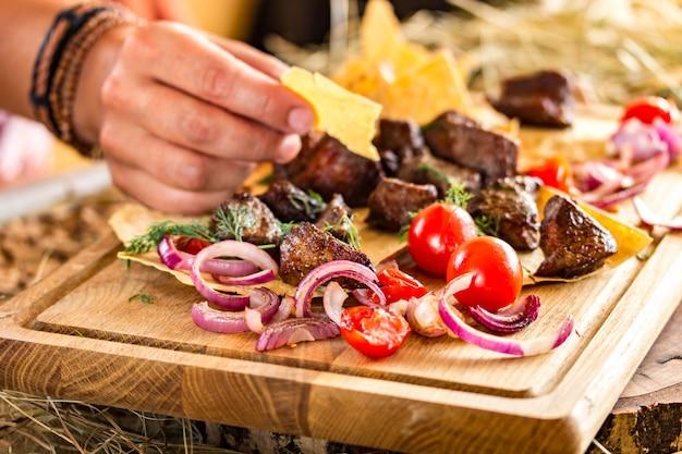 Fette di carne fritta con cipolle e pomodorini su una sottile torta piatta. la mano femminile prende un pezzo di torta. colori orizzontali e luminosi, spazio per il testo Foto Premium