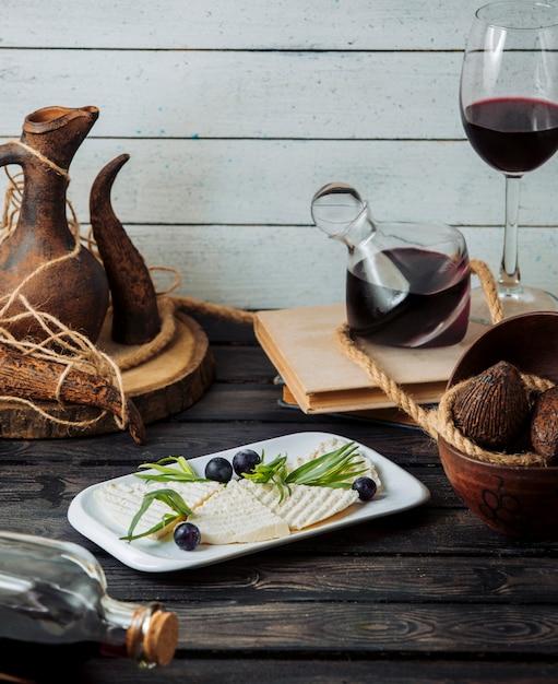Fette di formaggio bianco guarnite con uva e dragoncello servite con vino rosso Foto Gratuite