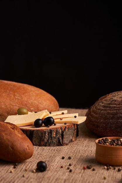 Fette di formaggio sullo scrittorio di legno fra i diversi pani Foto Premium