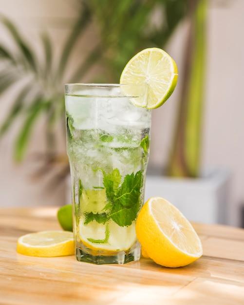Fette di frutta vicino bicchiere di bevanda con ghiaccio ed erbe sul tavolo Foto Gratuite