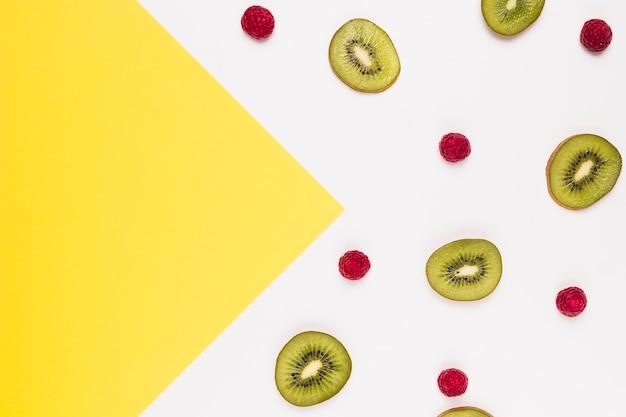 Fette di gustoso kiwi e lampone su sfondo multicolore Foto Gratuite