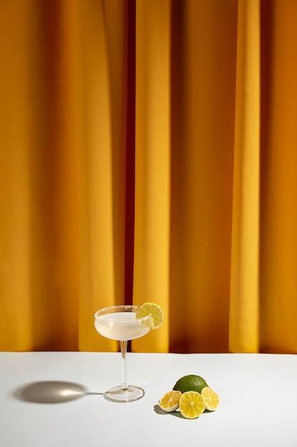 Fette di limone divise in due vicino al cocktail sul tavolo contro la tenda Foto Gratuite