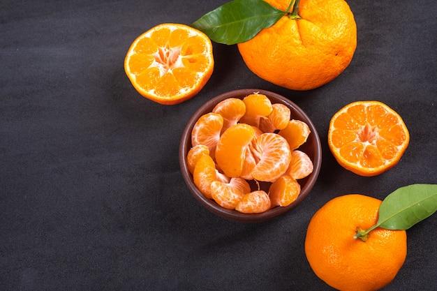 Fette di mandarino in ciotola di ceramica sulla superficie nera Foto Gratuite
