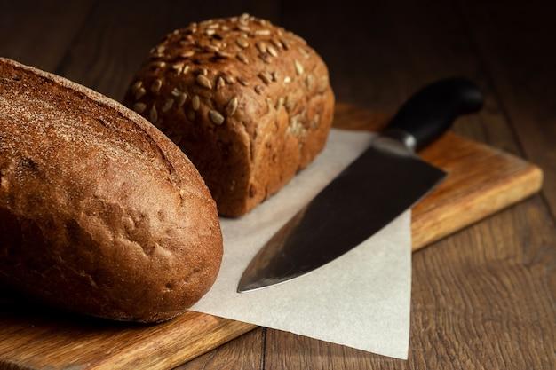 Fette di pane di segale e un coltello primo piano, su un tagliere di legno Foto Premium